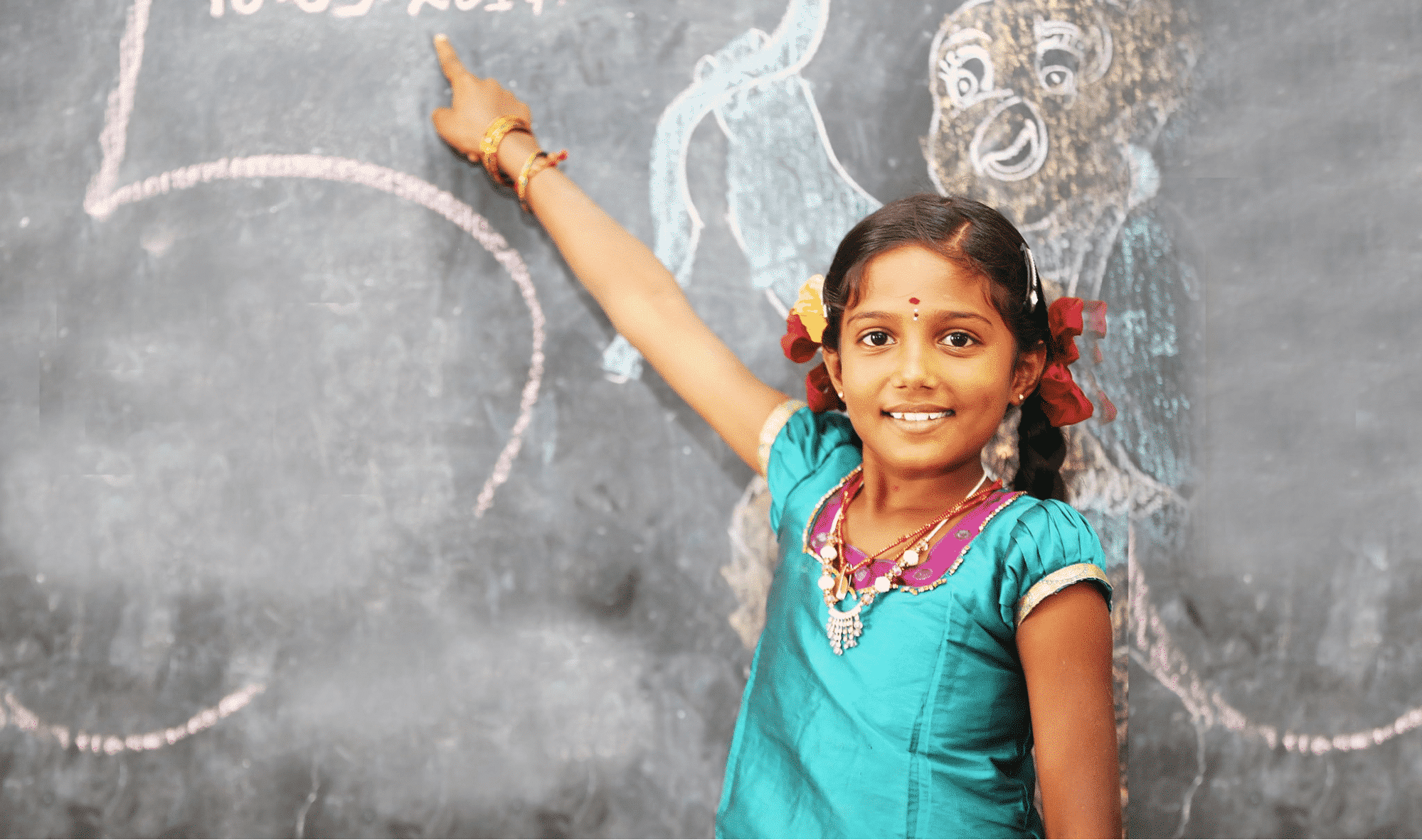 Girl smiling and pointing at artwork on chalk board